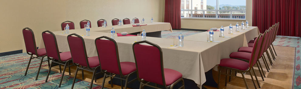 A spacious event room with tables set up in a U shape for a meeting at the Days Inn Stephenville hotel