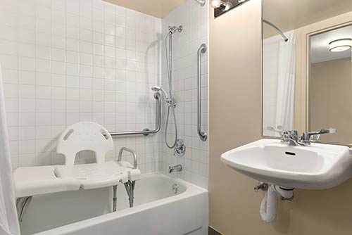 A large accessible bathroom at the Days Inn Stephenville hotel located near the St. George blueberry festival