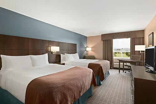 A spacious double queen bedroom at the Days Inn Stephenville hotel located near the St. George blueberry festival