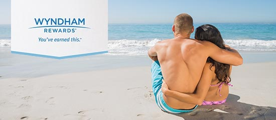 A couple sitting on the beach signifying the Wyndham rewards you can earn by stay at the Days Inn Stephenville hotel